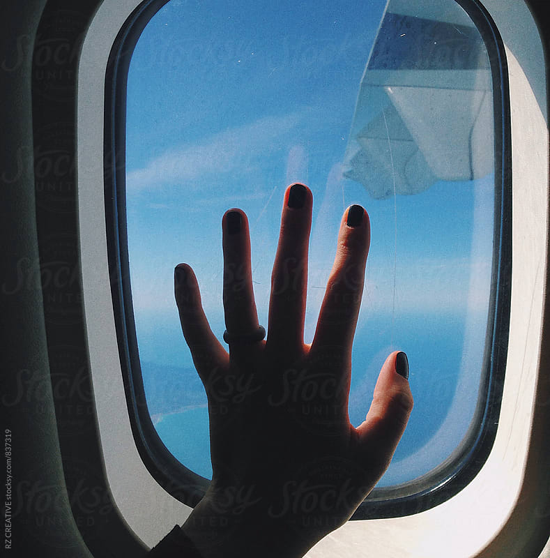 Female hand pressed against a plane window. by RZ CREATIVE for Stocksy United