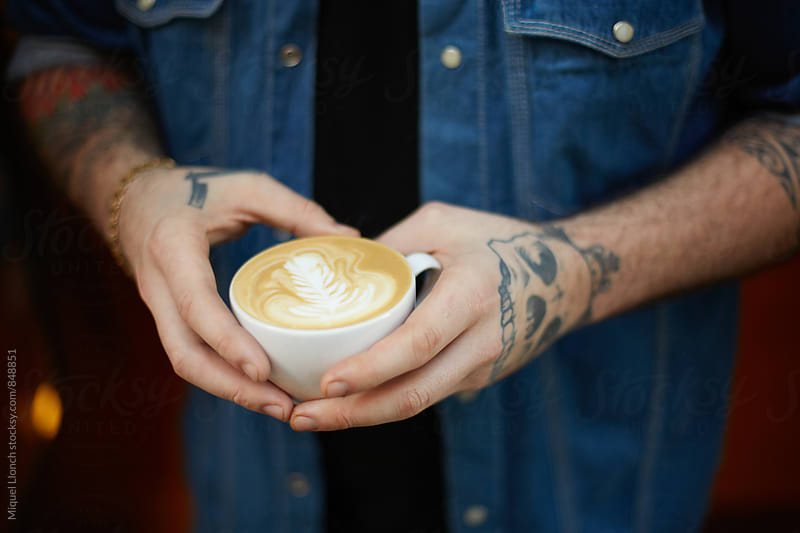 Male tattooed hands holding a cup of coffee by Miquel Llonch for Stocksy United
