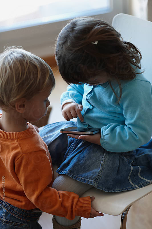 Children playing with mobile phone by Miquel Llonch for Stocksy United