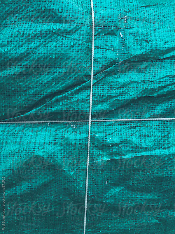 Rope covering green tarpaulin, close up by Paul Edmondson for Stocksy United