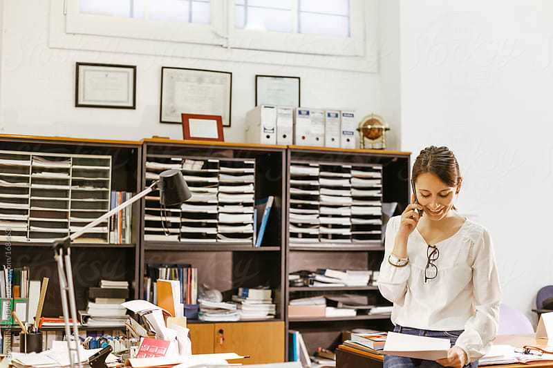 Businesswoman at phone working in her office. by BONNINSTUDIO for Stocksy United