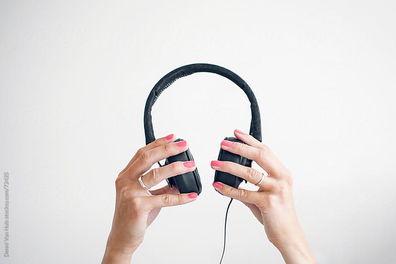 Two female hands holding up headphones in front of a white wall by Denni Van Huis for Stocksy United
