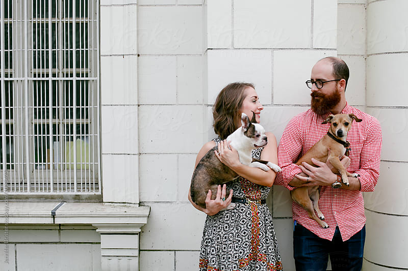 Couple holding small dogs  by Jennifer Brister for Stocksy United