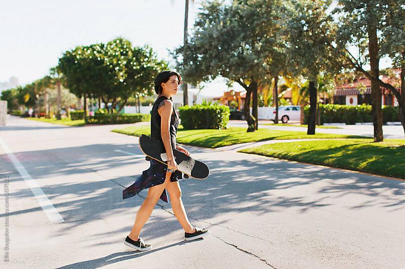 Skater girl walking across the street by Ellie Baygulov for Stocksy United