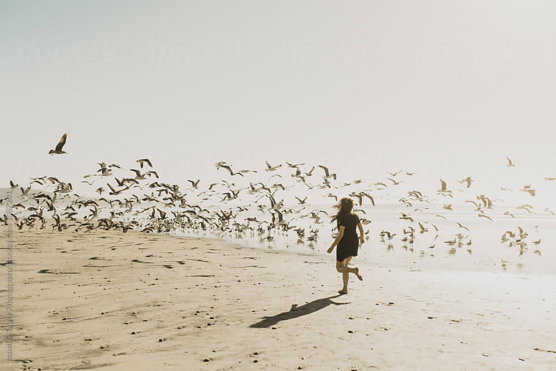 Girl running with Seagulls  by Isaiah & Taylor Photography for Stocksy United