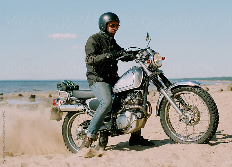 Man riding a motorcycle on sandy beach by Lyuba Burakova for Stocksy United