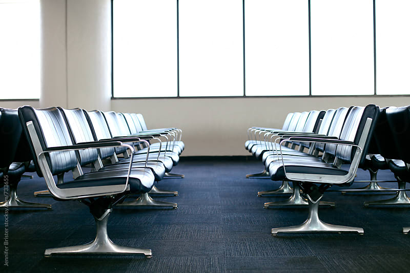 Row of chairs at airport by Jen Brister for Stocksy United