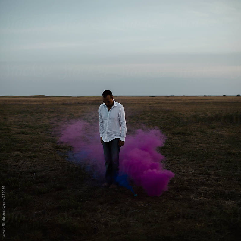 Man standing in a purple smoke in nature by Jovana Rikalo for Stocksy United