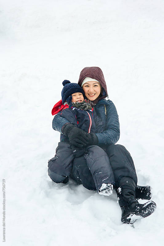 Mother and her little child having fun, hugging and posing for the camera in the snow by Lawrence del Mundo for Stocksy United