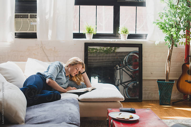 Young woman reading at home by Lauren Naefe for Stocksy United