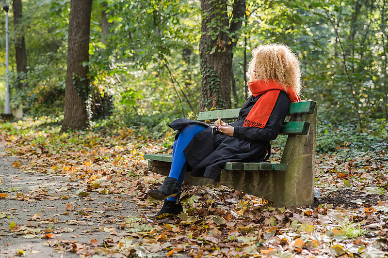 Woman sitting on a bench in a park on a autumn day by Jovo Jovanovic for Stocksy United