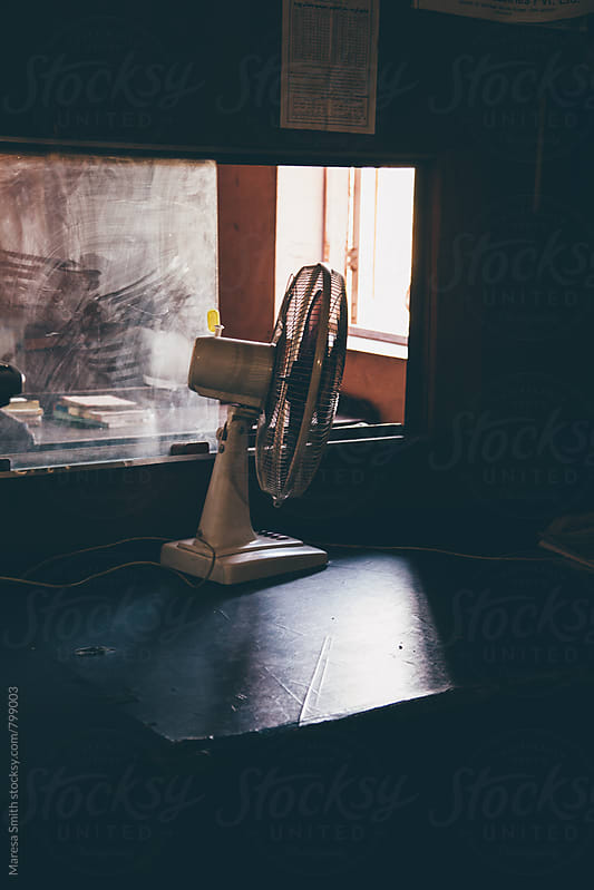 A dusty window and a fan in an office in India by Maresa Smith for Stocksy United
