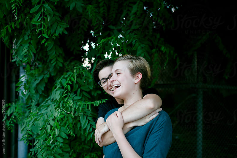 Two women laugh and embrace by Jen Brister for Stocksy United