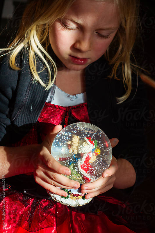 A little girl with a Christmas snow globe by Helen Rushbrook for Stocksy United