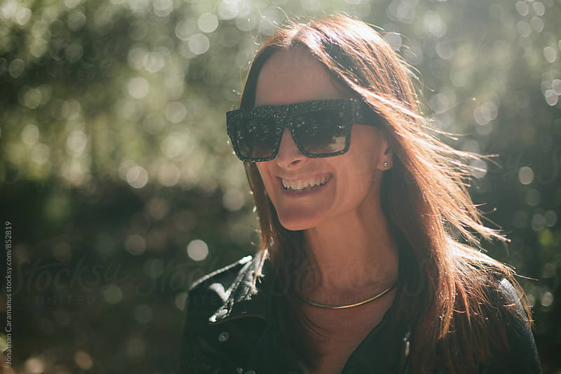 Portrait of young woman wearing big designer sunglasses in nature with leather jacket by Jonathan Caramanus for Stocksy United