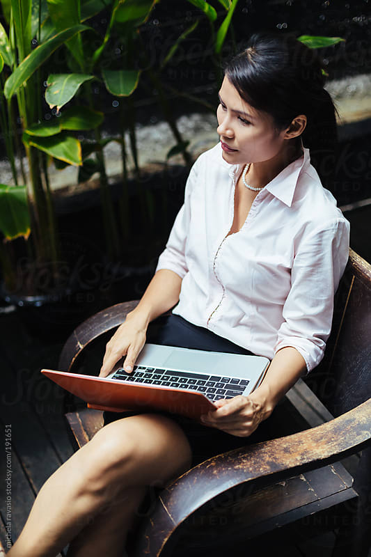 Elegant woman sitting outdoors with her laptop by michela ravasio for Stocksy United