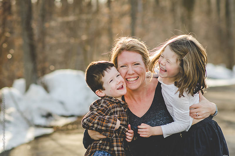 Mom tickling happy kids at the park by Lindsay Crandall for Stocksy United