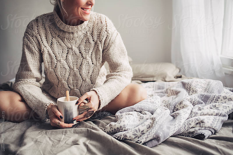 Smiling Woman Drinking Coffee in Bed  by Lumina for Stocksy United