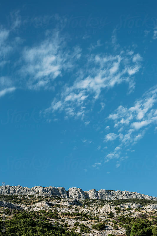 Dry rocky land with some vegetation and the big blue sky by Beatrix Boros for Stocksy United