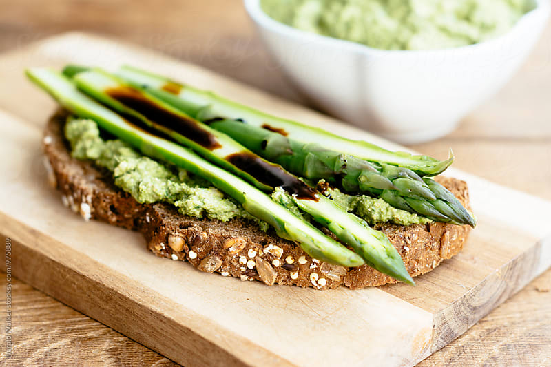 Asparagus and kale pesto toast by Harald Walker for Stocksy United