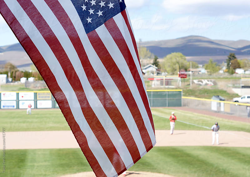 The American flag waving with a rural town's baseball game in the background.  by Tana Teel for Stocksy United
