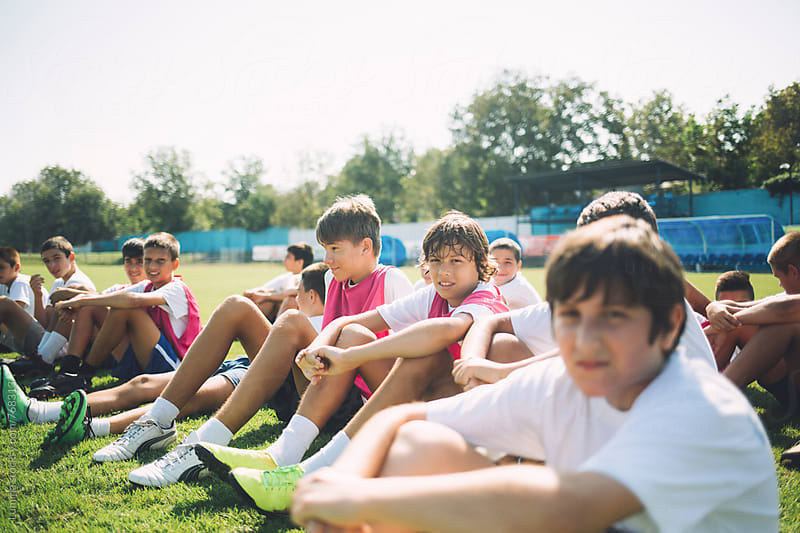 Young Football Players Sitting on the Ground by Lumina for Stocksy United