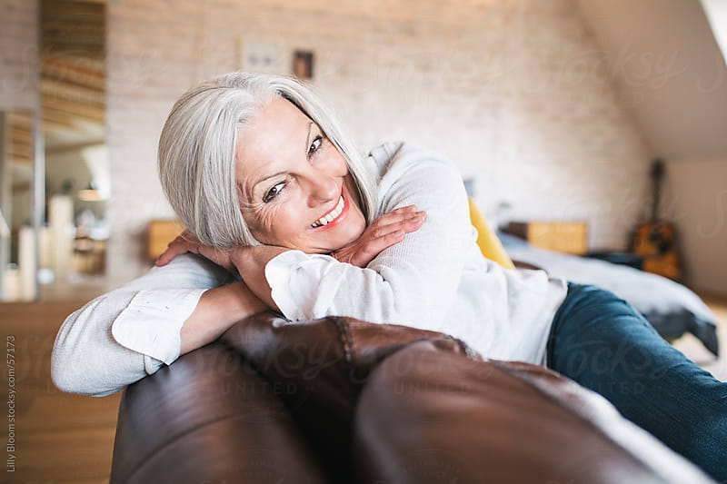Senior woman on a sofa, relaxing. by Lilly Bloom for Stocksy United