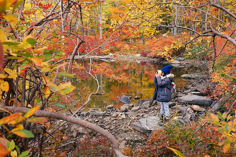 Young boy peers out at lake through binoculars by Kelli Seeger Kim for Stocksy United