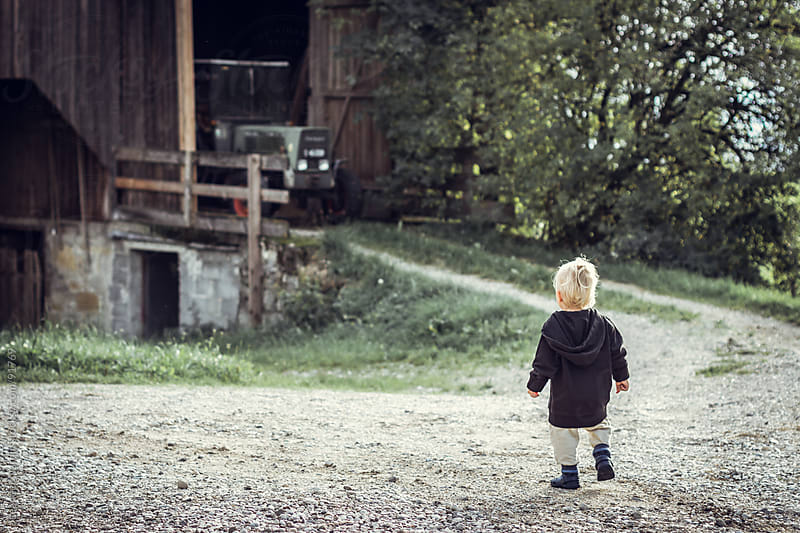 Blonde, little boy walks straight to a tractor on a farm by Leander Nardin for Stocksy United