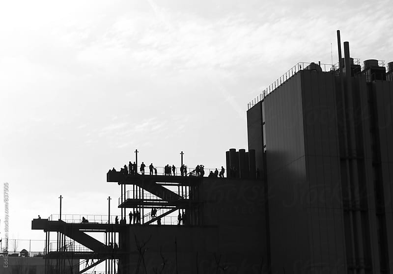 Silhouette of people hanging out on a rooftop  by Eddie Pearson for Stocksy United