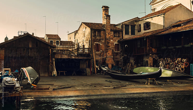 Small local rustic gondola restoration workshop on docks.Venice/Italy by Audrey Shtecinjo for Stocksy United
