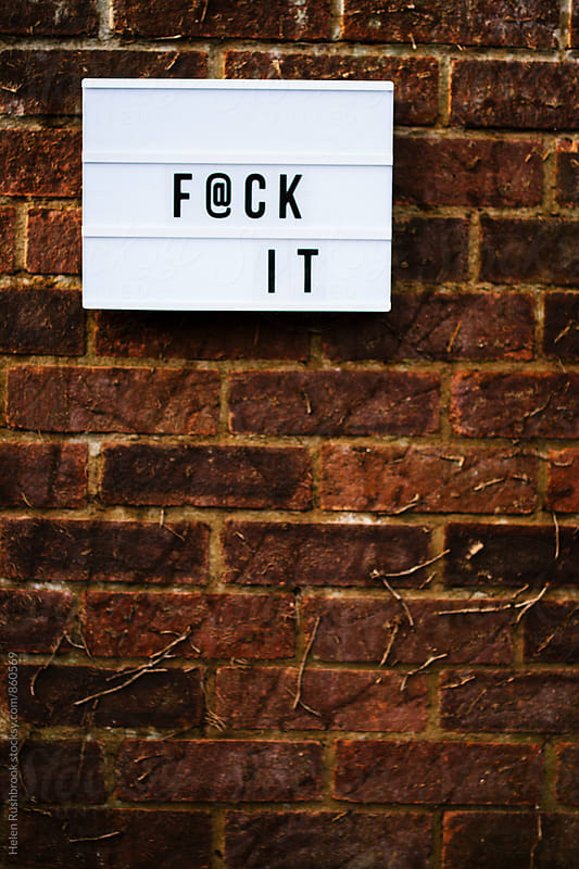 The words F@ck It spelled out on a cinematic lightbox on a brick wall. by Helen Rushbrook for Stocksy United