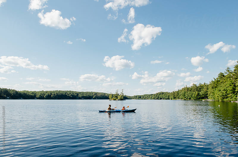 Father and son kayak together on a lake by Cara Dolan for Stocksy United