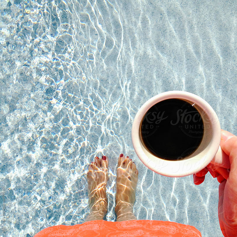 Woman standing in pool while drinking coffee by Holly Clark for Stocksy United