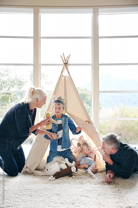 Family playing in teepee tent in living room together.  by Trinette Reed for Stocksy United