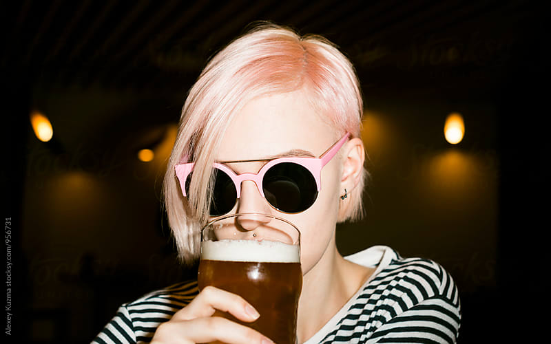 cool young woman with pink hair drinking a beer by Vesna for Stocksy United