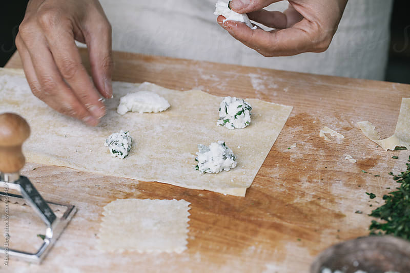 Woman filling with ricotta and spinach fresh ravioli pasta by Alberto Bogo for Stocksy United