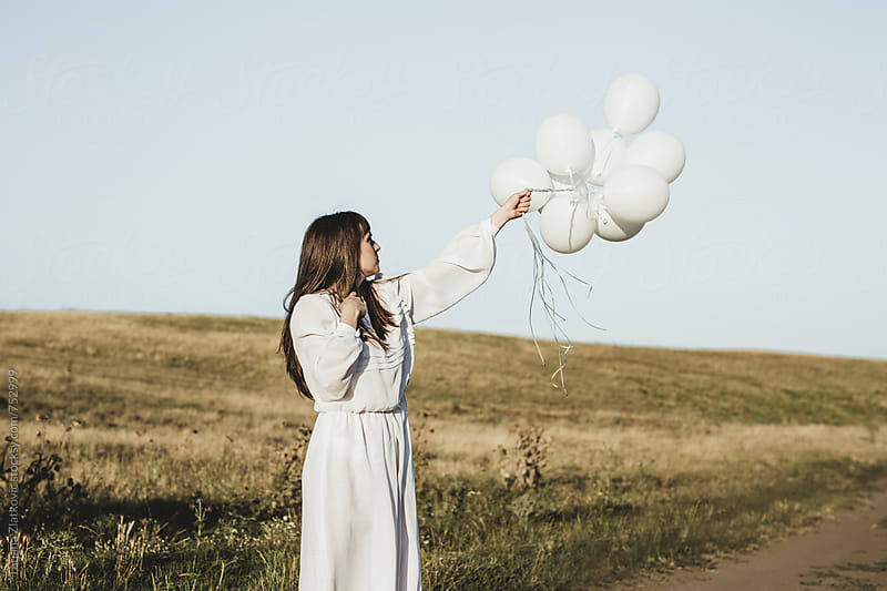 Young woman with white balloons by Tatjana Ristanic for Stocksy United