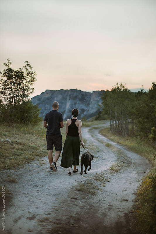 Back view of a couple walking with their dog on the mountain by Ani Dimi for Stocksy United