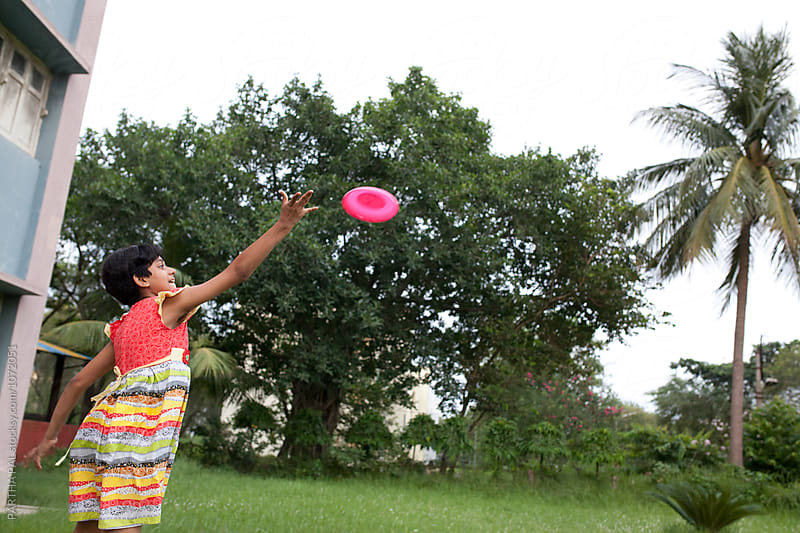 Teenage girl playing with flying disc by PARTHA PAL for Stocksy United