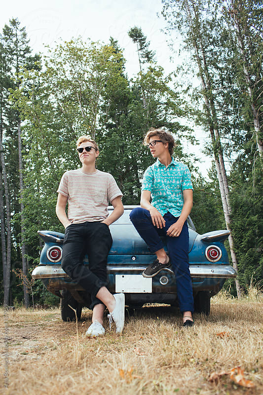 Two boys leaning on the back of a blue car by Ania Boniecka for Stocksy United