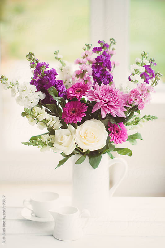 Purple and white flower bouquet in a white jug by Ruth Black for Stocksy United