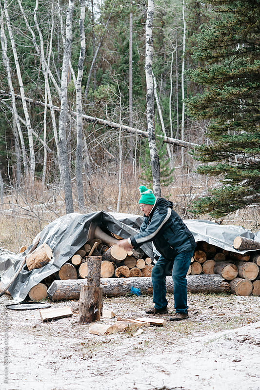 Senior Man Chopping Wood by Ronnie Comeau for Stocksy United
