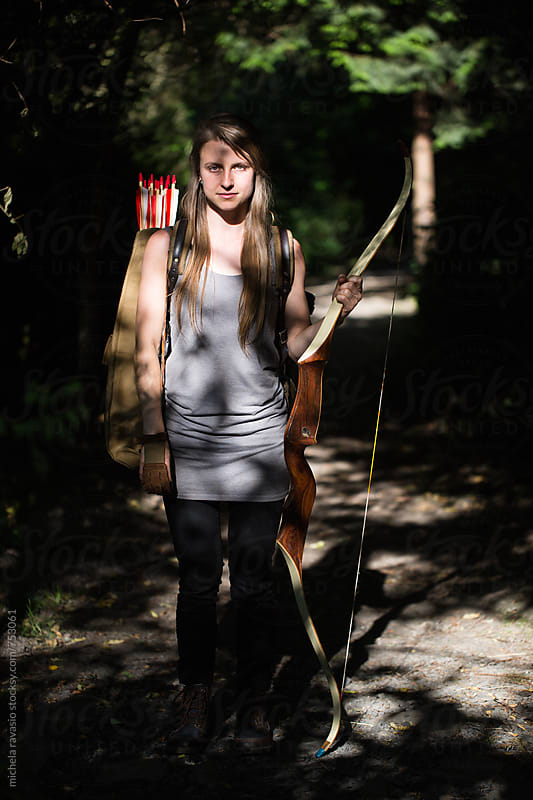 Portrait of archer with bow and arrow by michela ravasio for Stocksy United
