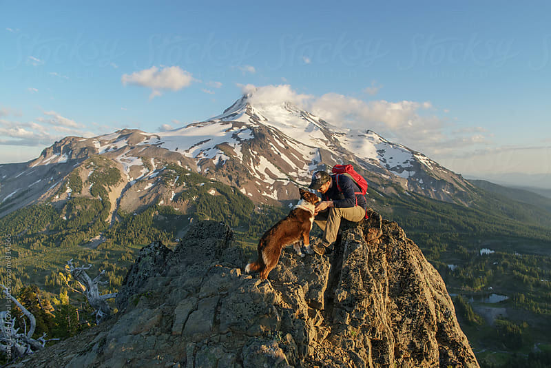 Man and dog high up at sunset with mountain behind them by Isaac Lane Koval for Stocksy United