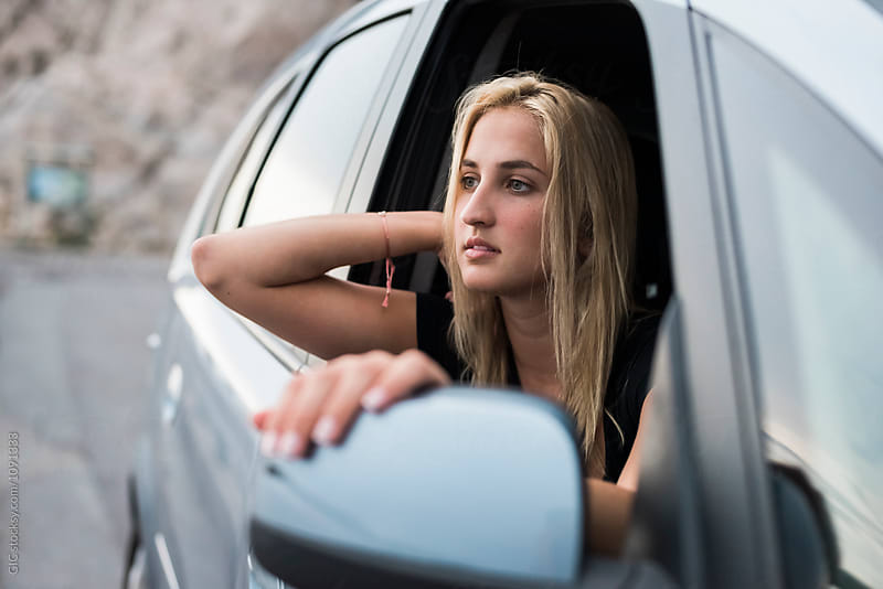 Young woman traveling by car by Simone Becchetti for Stocksy United