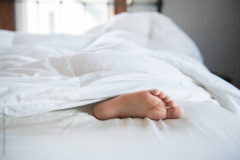 Feet stick out of  white bed covers by Cara Dolan for Stocksy United
