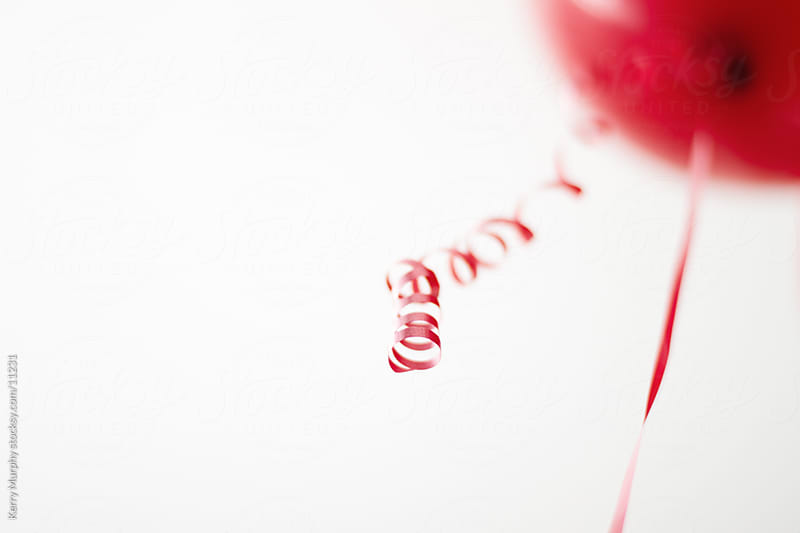 Single red party balloon by Kerry Murphy for Stocksy United