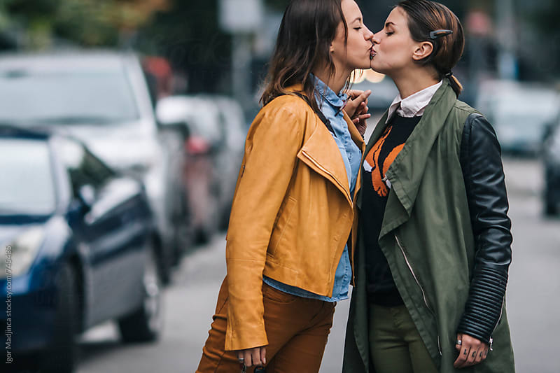two colorfully dressed girls in love kissing on the street, homosexual by Igor Madjinca for Stocksy United
