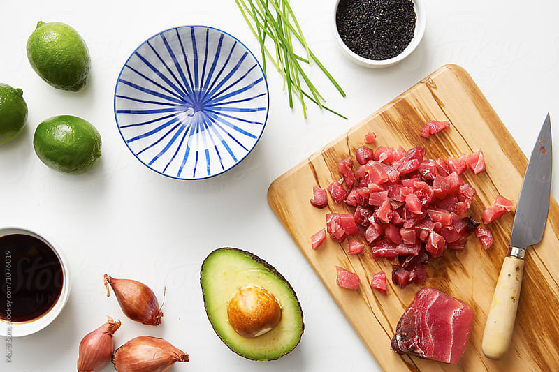 Chopped tuna,avocado and lime on table by Martí Sans for Stocksy United